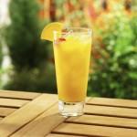 Orange cocktail with maraschino cherry garnish, outdoor backyard setting.